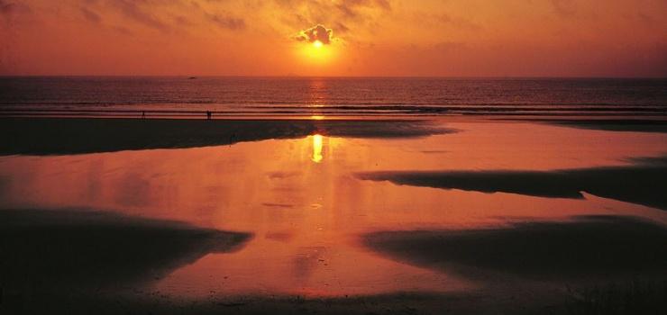 """桃花岛东南的千步金沙长1370米,宽400余米,从面积来说,是舟山群岛第二大沙滩。滩地平缓,从沙质方面来书是进行海浴、沙浴、阳光浴和沙滩漫步较理想、优质的沙滩。千步金沙属细型沙质,细软纯净,与普陀山的白步沙、千步沙和嵊泗的基湖沙滩相比较要细软得多,与朱家尖的东沙、南沙相似,但还要松软一些,且沙滩上沿有部分植被覆盖,这一点其它沙滩是很难找到的。夏秋季,每当星辰消失,旭日钻出海面,海天、沙地浑然一体,形成""""金沙日出""""天象景观。"""